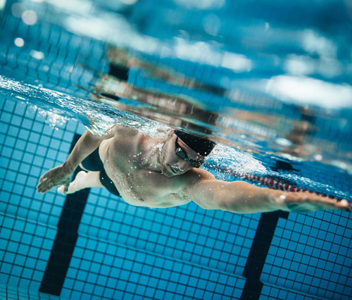 swimming coach helping you work on your stroke